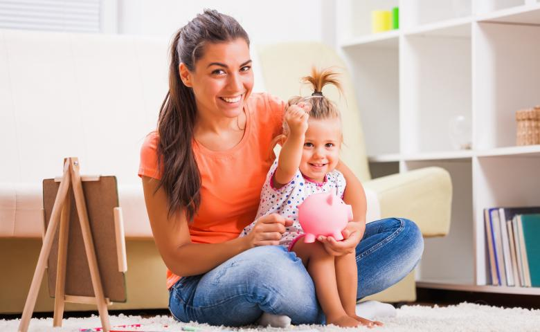 Mother and daughter sitting on floor with piggybank